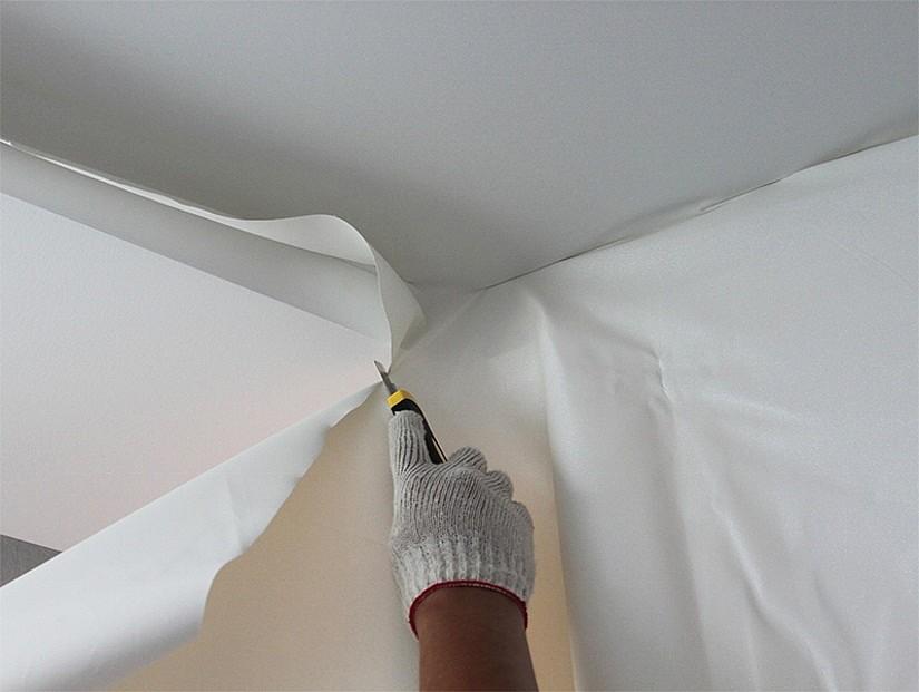 Удаление лишней ткани в конце монтажа тканевых потолков